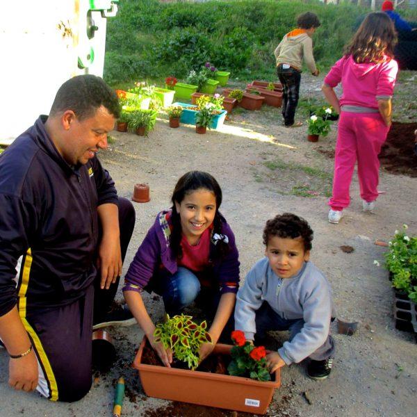 Adulte qui aide enfants pour plantations