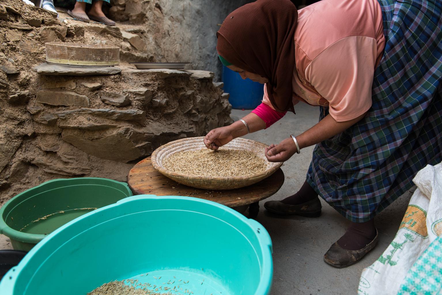 Femme triant du grain dans un tamis